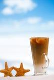 与海星的被冰的咖啡拿铁在海滩海洋和海景 库存照片