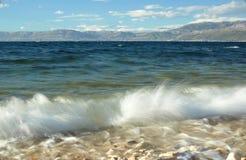 与海波浪的美丽的蓝色达尔马希亚海岸 库存照片