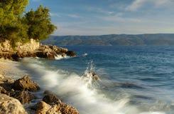 与海波浪的美丽的蓝色达尔马希亚海岸 库存图片