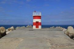 与海洋对比的小船灯塔 库存照片