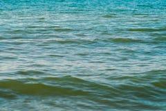 与海浪的海沙滩在日落 免版税库存照片