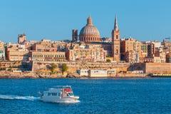 与海湾巡航小船,马耳他的瓦莱塔citiscape 图库摄影