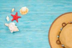 与海滩帽子的红色海星和海壳 库存图片