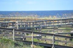 与海燕麦的波浪形成显明对比,海滩木板走道的直线是 库存照片