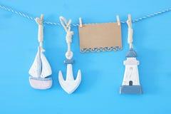 与海生活方式装饰的船舶概念:垂悬在串的帆船和船锚在蓝色木背景 免版税库存照片