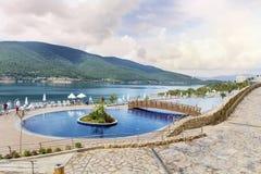 与海的大室外豪华游泳池周围在背景中 免版税图库摄影