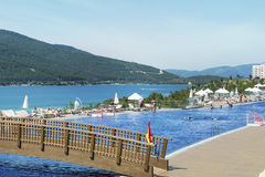 与海的大室外豪华游泳池周围在背景中 免版税库存照片