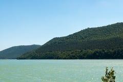 与海的绿色山在它旁边 免版税图库摄影
