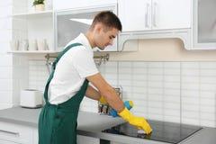 与海绵的男性管理员清洁厨灶 库存照片