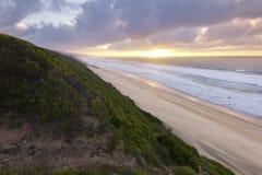 与海滩和云彩的沿海日出 免版税图库摄影