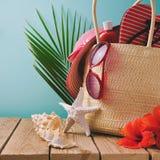 与海滩项目的暑假袋子在木桌上 免版税库存图片