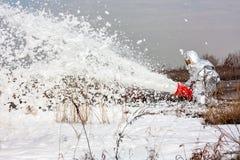 与消火泡沫的消防员倾吐的火焰 免版税库存图片