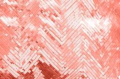 与淡光的珊瑚衣服饰物之小金属片的织品纹理 库存图片