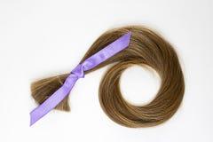 与淡紫色丝带的长的金发捐赠作为战斗的标志与癌症的在白色背景 r r 图库摄影
