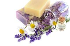 与淡紫色和春黄菊花的温泉产品在白色背景 免版税库存图片