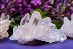 与淡紫色花围拢的赤铁矿包括的喜马拉雅清楚的石英群 图库摄影