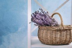 与淡紫色花的柳条筐在架子 库存图片