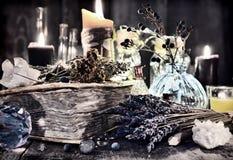 与淡紫色花,不可思议的礼节对象,医治草本,水晶和黑蜡烛的古色古香的巫婆书 图库摄影