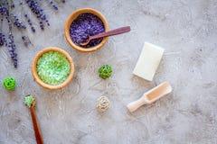 与淡紫色草本化妆盐浴的和肥皂的家庭温泉在石书桌背景顶视图 免版税图库摄影