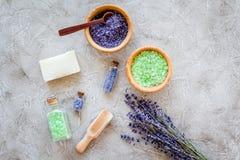 与淡紫色草本化妆盐浴的和肥皂的家庭温泉在石书桌背景顶视图 库存图片