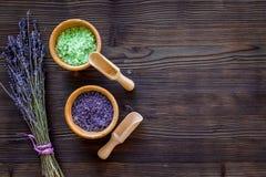 与淡紫色草本化妆盐的家庭温泉在木书桌背景顶视图大模型的浴的 免版税库存图片