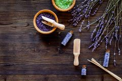 与淡紫色草本化妆盐的家庭温泉在木书桌背景顶视图大模型的浴的 库存照片