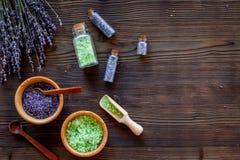与淡紫色草本化妆盐的家庭温泉在木书桌背景顶视图大模型的浴的 免版税图库摄影