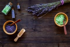 与淡紫色草本化妆盐的家庭温泉在木书桌背景顶视图大模型的浴的 免版税库存照片