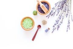 与淡紫色草本化妆盐的家庭温泉在白色书桌背景顶视图大模型的浴的 图库摄影