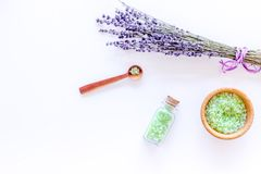 与淡紫色草本化妆盐的家庭温泉在白色书桌背景顶视图大模型的浴的 免版税库存照片