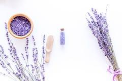 与淡紫色草本化妆盐的家庭温泉在白色书桌背景顶视图大模型的浴的 免版税库存图片
