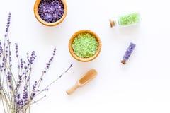 与淡紫色草本化妆盐的家庭温泉在白色书桌背景顶视图的浴的 免版税库存图片