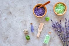 与淡紫色草本化妆盐的家庭温泉在石书桌背景顶视图大模型的浴的 免版税库存照片