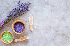 与淡紫色草本化妆盐的家庭温泉在石书桌背景顶视图大模型的浴的 免版税库存图片