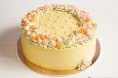 与淡色奶油色花的淡黄的奶油甜点蛋糕 免版税图库摄影