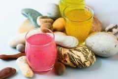 与淡色果汁饮料的三块玻璃放在堆各种各样的装饰小卵石之间 库存照片
