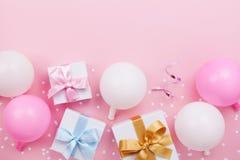 与淡色气球的生日桌、礼物或者当前箱子和五彩纸屑顶视图 平的位置构成 库存照片
