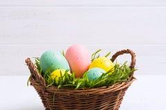 与淡色的复活节彩蛋与在篮子的绿草有白色木背景 免版税库存照片