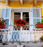 与淡色蓝色快门和明亮的红色花的老阳台门道入口 库存图片