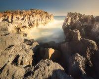 与淡色skyand的岩石岸挥动伊维萨岛,西班牙 图库摄影