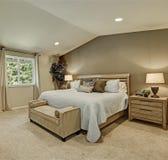与淡蓝的卧具的典雅的米黄和棕色卧室内部 库存照片