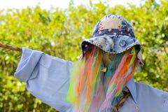 与淡蓝的衬衣的滑稽的五颜六色的彩虹滤网稻草人 免版税库存图片