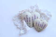 与淡紫色图片和有花边的餐巾的两心脏在白色背景 软的焦点,明亮的颜色 免版税库存图片