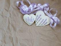 与淡紫色图片和紫色丝带的两心脏在老纸背景  软的焦点,背景方式 库存照片