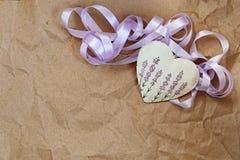 与淡紫色图片的装饰心脏和在老纸背景的紫色丝带  免版税库存照片
