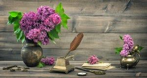 与淡紫色花和古色古香的文字工具的静物画 库存图片
