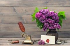 与淡紫色花和古色古香的辅助部件的静物画 免版税库存图片