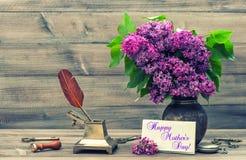 与淡紫色花和古色古香的辅助部件的静物画 库存照片