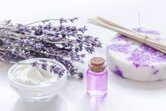 与淡紫色花和油的有机化妆用品在白色背景 库存照片