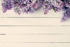 与淡紫色花的葡萄酒木背景 库存照片